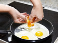 Woman breaks an egg in fried eggs