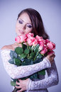 Woman in bridal dress with bouquet from roses Royalty Free Stock Image