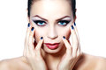 Woman with brightly blue eyes face of a beautiful young and smoky make up touching her face hands Stock Images
