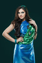 Woman in brilliant blue-green dress with peacock feathers design. Creative fantasy makeup, long dark hair.