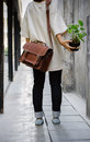 Woman with brown leather bag and hold the plant Stock Image