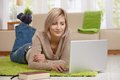 Woman browsing internet on laptop attractive young at home in living room computer smiling Royalty Free Stock Images