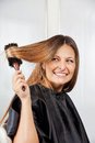 Woman brushing hair in salon happy mid adult Stock Photography