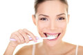 Woman brushing teeth holding toothbrush dental care close up portrait of beautiful girl smiling happy looking at Stock Photos