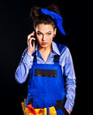 Woman builder calling mobile phone. Royalty Free Stock Photography