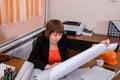 Woman builder engineer looking at blueprint paper