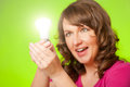 Woman with bulb in hand could be a concept of new idea or ecology because of green background Stock Photography