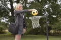 stock image of  Woman in business suit and netball net scoring a goal