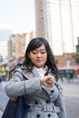 Woman on busy street young asian checking her watch a in a large city Stock Photos