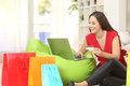 Woman buying online with credit card at home a and multiple shopping bags beside Royalty Free Stock Photography