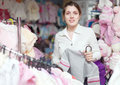 Woman buys clothes for her little daughter in children s clothing store Royalty Free Stock Photo