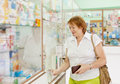 Woman buys drugs at the pharmacy mature Royalty Free Stock Photography