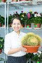 Woman with cactus in flower store happy mature Royalty Free Stock Image