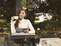 Woman in cafe young sitting next to windows drinking coffee with tablet computer hand Royalty Free Stock Photos