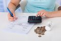 Woman calculating invoice by coins and thermostat at desk Royalty Free Stock Photo
