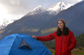 Woman camping outdoors portrait of a young under a high snow capped mountain during sunset Stock Image