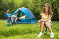 Woman on camping young women sits in front of the tent a green with her friend in the background reading a book Royalty Free Stock Photo