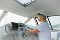 Woman captain the the behind a yacht steering wheel Royalty Free Stock Photography