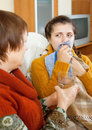Woman caring for her adult daughter has cough in living room Stock Images