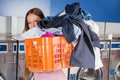Woman carrying basket full of dirty clothes portrait young in laundry Stock Photos