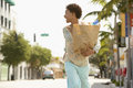 Woman carrying grocery bag while walking on street cheerful african american Royalty Free Stock Photos