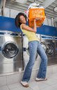 Woman carrying heavy basket of clothes portrait happy young in laundromat Stock Image