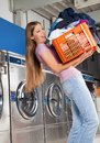 Woman carrying heavy basket of clothes side view young in laundromat Stock Photos