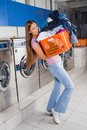 Woman carrying heavy basket of clothes young in laundry Royalty Free Stock Photography