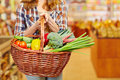 Woman carrying shopping basket in supermarket full of vegetables a Stock Image