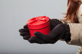 Woman carrying a small round red gift box close up of hands wearing gloves Stock Photography