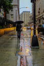 A woman carrying an umbrella and walking down a street in the rain following the Boston Freedom Trail.