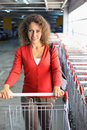 Woman with cart standing in indoor car park Royalty Free Stock Photo