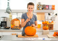Woman carving a pumpkin Jack-O-Lantern for Halloween party Royalty Free Stock Photo