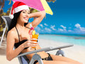 Woman celebrating the new year at the beach happy a beautiful girl in santa hat with a refreshing drink in hand Stock Images