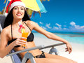 Woman celebrating the new year at the beach happy a beautiful girl in santa hat with a refreshing drink in hand Stock Photo