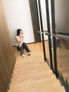 Woman on cell phone at bottom of stairs full length young women Royalty Free Stock Photos