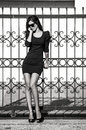 Woman with cell phone fashion talk on lean on fence wearing sunglasses and tight dress full body shot bw Stock Photos