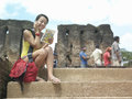 Woman with cellphone and guidebook against old ruins young using on stairs while reading Stock Photo