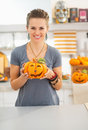 Woman with ceramic pumpkin in halloween decorated kitchen ready to invasion smiling young showing Royalty Free Stock Photo