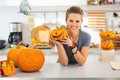 Woman with ceramic pumpkin in halloween decorated kitchen ready to invasion smiling young showing Stock Photography
