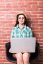 Woman on chair in casual wear is using a laptop beautiful young and smiling sitting against white brick wall Royalty Free Stock Images