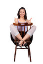 Woman with chair long haired brunette is sitting on a legs crossed has raised fingers isolated on white background Royalty Free Stock Photo