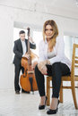 Woman on chair and man plays melody young women stool men Royalty Free Stock Images