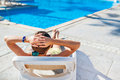 Woman chaise longue on the background of the pool at the hotel Royalty Free Stock Photos