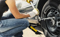 Woman changing tire car is of her with wheel wrench Royalty Free Stock Image