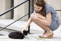 Woman in checkered dress fondle street cat Royalty Free Stock Photo