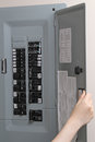 Woman checking automatic fuses at electrical control panel home Royalty Free Stock Images
