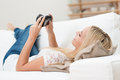 Woman checking her images on the camera blond lying back a sofa back of a digital Royalty Free Stock Photo