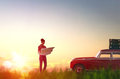 Woman checks the route toward adventure beautiful young on a map on sunset background Stock Photography