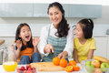 Woman with cheerful two daughters cutting fruit in kitchen portrait of a smiling women the at home Royalty Free Stock Photo